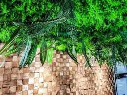 Holzpaneel mit Kunstpflanzen